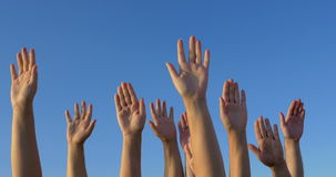 Raised hands against blue sky stock video