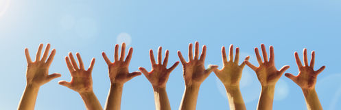 Raised hands. On a blue sky background with copy space stock images