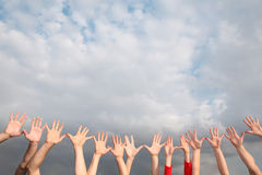 Raised hands on cloudy sky Stock Photo