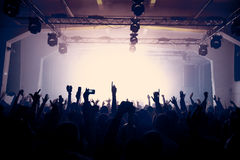 Raised hands on the concert in an old venue. Vintage photo of a raised hands shillouetes at the rock concert, clubbing or celebrating New Year's eve. Active Royalty Free Stock Image