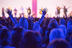 Raised Hands Concert. Open hands raised up in foreground with anonymous guitar player on stage in background stock image