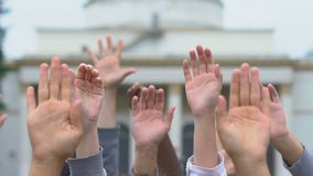 Raised hands on government building background, voting on democratic elections