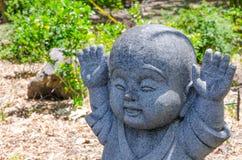 Raised hands up motion of Jizo little stone buddha statue. A Raised hands up motion of Jizo little stone buddha statue royalty free stock photography