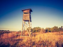 Raised hide on field. Beautiful field landscape with hunters raised hide. Photo with vintage mood effect Stock Image