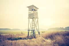 Raised hide on field. Beautiful field landscape with hunters raised hide. Photo with vintage mood effect Stock Photos