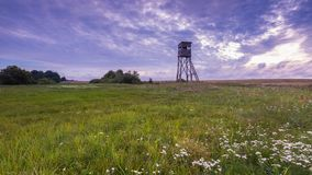 Raised hide on morning meadow. Under cloudy sky. Beautiful rural landscape Stock Image