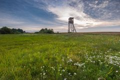 Raised hide on morning meadow. Under cloudy sky. Beautiful rural landscape Stock Images