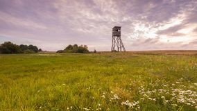 Raised hide on morning meadow. Under cloudy sky. Beautiful rural landscape Stock Photos