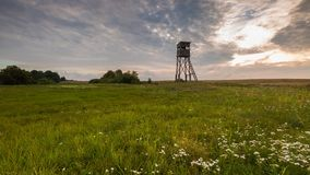 Raised hide on morning meadow. Under cloudy sky. Beautiful rural landscape Royalty Free Stock Images