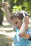 He raised his hand high and enjoy his favorite band. Little cute boy of pre-school age listens to music and shows satisfaction. He raised his hand high and enjoy Royalty Free Stock Images