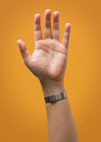 Raised Male Hand Isolated on Yellow Gold Orange Stock Photography