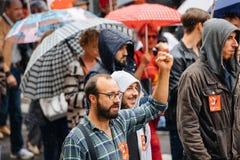 Raisen hand av den manliga personen som protesterar på Anti--makro protesten Arkivbild