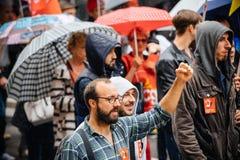 Raisen hand av den manliga personen som protesterar på Anti--makro protesten Arkivfoton