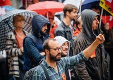 Raisen hand av den manliga personen som protesterar på Anti--makro protesten Arkivfoto