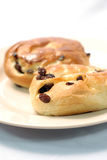 Raisin Buns on a Plate. Two fresh baked buns with raisins Royalty Free Stock Photography