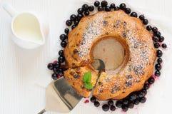 Raisin cake with icing sugar, flat lay. Ring raisin cake with icing sugar with one piece cut off and berries, flat lay Stock Photography
