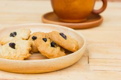 Raisin cookies on wooden table with brown coffee cup Royalty Free Stock Photos