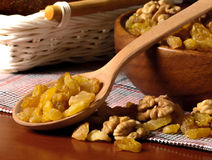 Raisin and peeled walnuts with wooden spoon and bowl Stock Photos