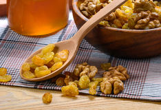 Raisin and peeled walnuts with wooden spoon, bowl and honey jar Royalty Free Stock Photos