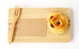 Raisin roll, note paper and fork on wooden tray isolated on whit Royalty Free Stock Photos