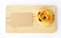Raisin roll and note paper on wooden tray isolated on white back Royalty Free Stock Images