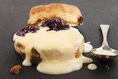 Raisin scone with fresh custard on slate Royalty Free Stock Photo