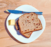 Raisin toast and butter. Raisin toast, butter, stainless knife and ceramic plate placed on wooden table Stock Photos