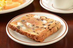 Raisin toast. Closeup of a plate of buttered raisin toast with a cup of coffee Royalty Free Stock Image