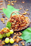 Raisin in a wicker basket and grape leaves Stock Photo