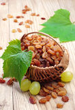 Raisin in a wicker basket and grapes with leaves Stock Images