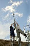 Raising an antenna. Two men raising an antenna for wireless devices Royalty Free Stock Images