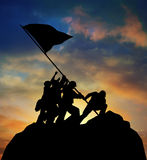 Raising the Flag. Silhouette of the image of soldiers raising the flag at Iwo Jima against a colorful sunset with clipping path Stock Image