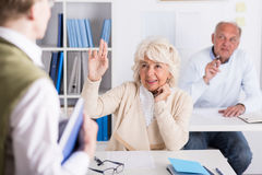 Raising hand to answer. Elderly female student is asking lecturer about something Stock Images