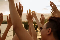 Raising hands to golden sunset sky Royalty Free Stock Photo