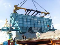 Raising the hopper car for unloading on a cargo ship. Lifting operations in the port. royalty free stock photo