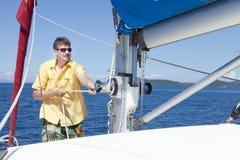 Raising the sail. Crew member of a sailboat is raising the sail Royalty Free Stock Image