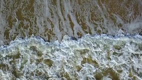Raising sand by waves of the transparent water becomes muddy the view from the top. Aerial survey. Slow motion. Raising sand by waves of the transparent water stock footage