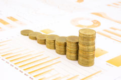Raising stacks of golden coins on business graph background. Raising stacks of golden coins on yellow business graph, data and report background, concepts of Stock Photos