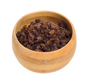 Raisins. A wooden bowl filled with raisins, isolated against a white background Stock Photo