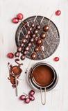 Raisins avec le lustre de chocolat sur des brochettes, préparation Photographie stock libre de droits
