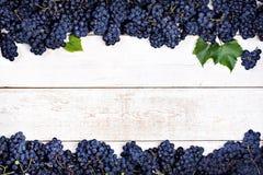 Raisins bleus sur de vieux conseils blancs Photos libres de droits