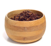 Raisins In A Bowl. A pile of raisins in a wooden bowl, isolated against a white background Stock Photography