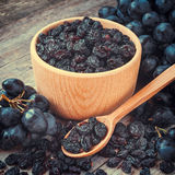 Raisins in bowl and blue grapes on table Stock Photography