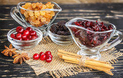 Raisins in a bowl, cranberries, cinnamon and anise on  wooden ta Royalty Free Stock Images