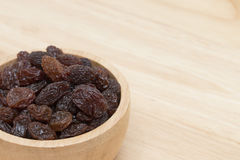 Raisins in bowl on wooden table Royalty Free Stock Photos