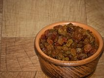 Raisins, in a brown clay plate on the table royalty free stock images