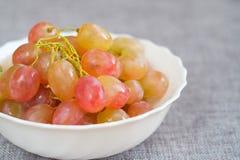 Raisins dans un plat de porcelaine Raisins de Muscat roses mûrs photos libres de droits