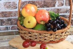 Raisins et pommes noirs juteux dans un panier avec le plan rapproché de baisses, photo stock