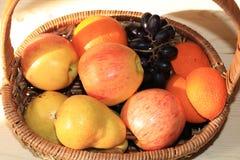 Raisins et pommes noirs juteux dans un panier sur la table images stock