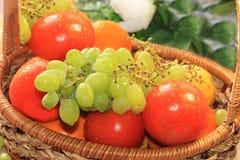 Raisins et tomates verts juteux dans un panier avec le plan rapproché de baisses, photographie stock